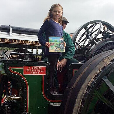 Happy fan of Victoria's Torton Tales on the footplate of Victoria with her book